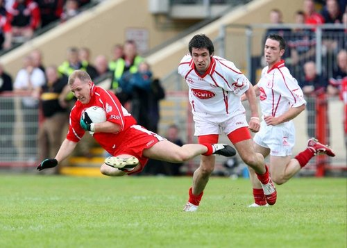 Johnny McBride of Derry is tackled by Tyrone's Joe McMahon