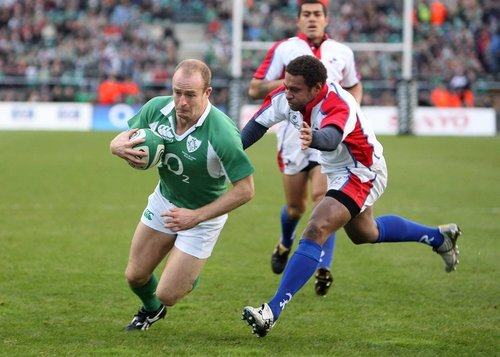 Ireland's Denis Hickie scores Ireland's first try as Pacific Islanders' Norman Ligairi closes in