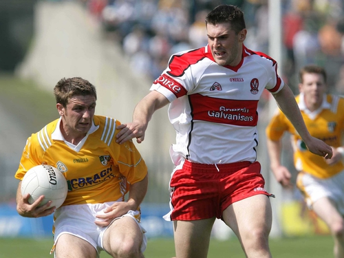 Derry goalscorer Mark Lynch tackles Tony Scullion of Antrim