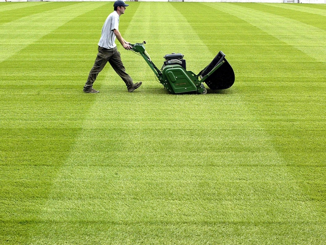 A groundsman cuts the grass in June 2002.
