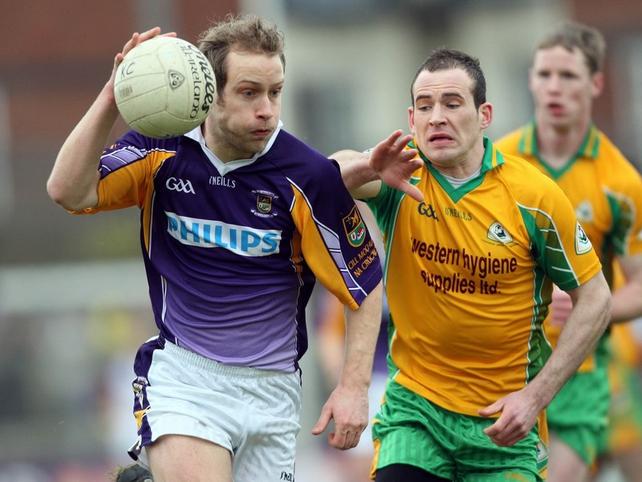 Brian Kavanagh of Crokes is harried by Corofin's Damien Burke