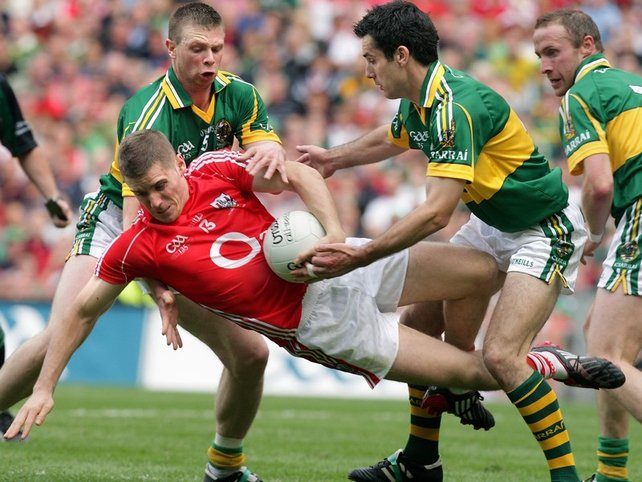 Daniel Goulding, who top scored for Cork with four points, is sent to ground by Kerry's Tomás Ó Sé and Tom O'Sullivan