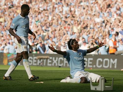 Emmanuel Adebayor celebrates in front of Arsenal supporters