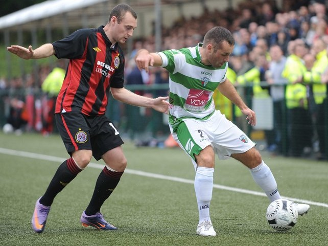 Mark Quigley of Bohemians fights to get the ball as Danny Holmes of TNS shields it