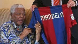 Nelson Mandela smiles as he receives a Barcelona Football Club jersey from club manager Albert Perrin at the Mandela foundation in Houghton on 20 June 2007