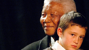 Nelson Mandela and Josh Kovarsky listen to the Soweto Gospel choir sing a song in praise of Mandela at a party to celebrate his 85th birthday