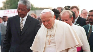 President Nelson Mandela walks with Pope John Paul II after the pontiff's arrival in 1995 on his first official visit to South Africa