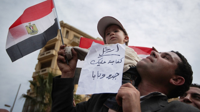 Egypt - An anti-govt protestor holds his child aloft in Tahrir Square