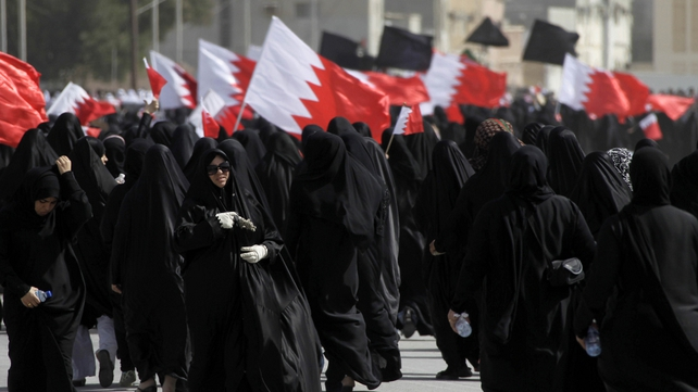 Bahrain - Shia women wave flags as they attend funerals of killed protestors