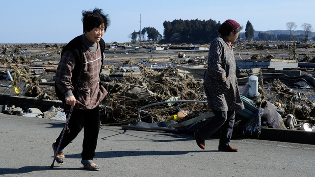 Local residents look at debris brought by the huge tsunami in Minamisoma, Fukushima