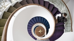 A classy spiral staircase weaves through three floors