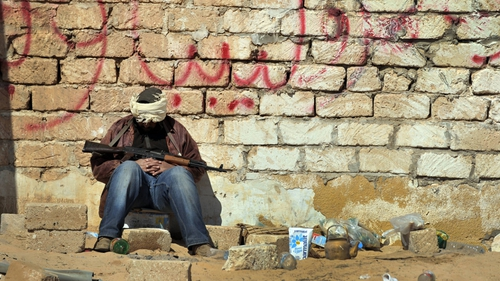 A rebel fighter rests at a checkpoint outside the city of Ajdabiya