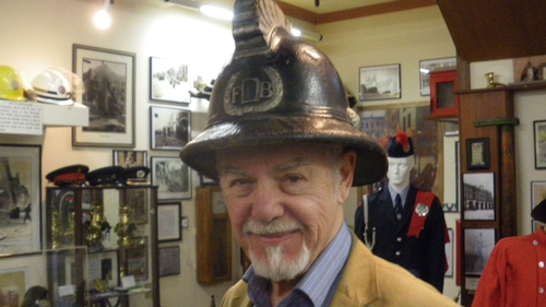 Paddy O'Flaherty in Dublin Fire Brigade Museum. The helmet was worn in Belfast in 1941 by District Officer Michael Rogers.