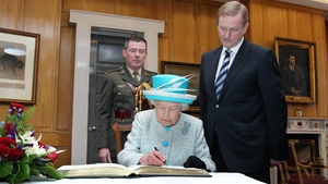 Taoiseach Enda Kenny watches as the Queen signs the visitor's book at Government Buildings