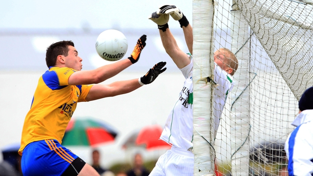 Leitrim goalkeeper Cathal McCrann punches the ball away under pressure from Roscommon's Donie Shine