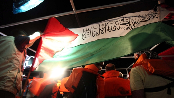 Mavi Marmara - Turkish human-rights activist hold a Palestinian flag hours before the Israeli Navy attack