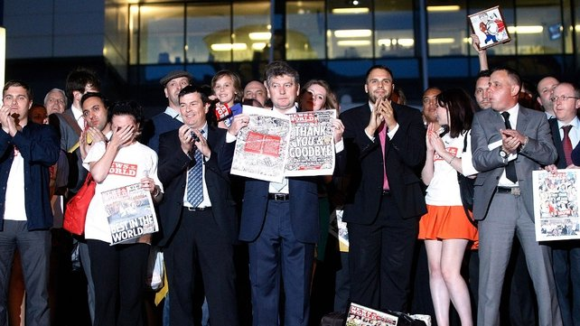 London - Editor Colin Myler (centre, holding paper) leads staff and journalists out of the News International offices