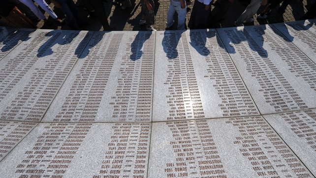 Bosnian Muslims walk past a memorial marble plates with the names of the victims