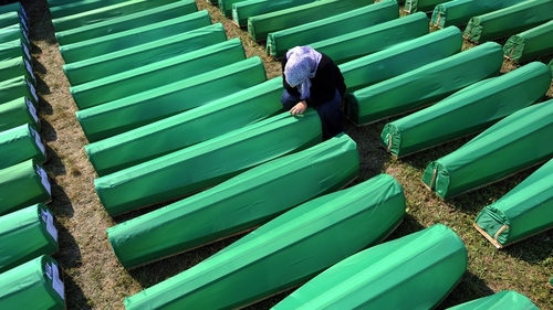 A Bosnian Muslim woman cries over one of the 613 coffins before a mass burrial ceremony at the Potocari Memorial Cemetery