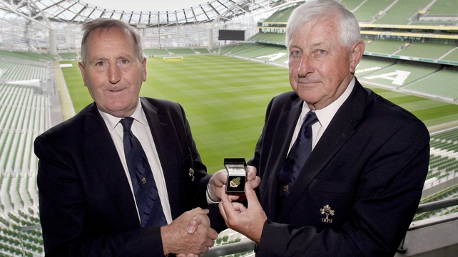 Outgoing IRFU president Caleb Powell (left) hands over the badge of office to John Hussey