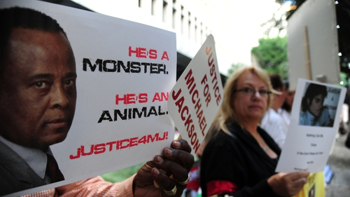 Supporters at the late pop star Michael Jackson hold signs outside Los Angeles Superior Court