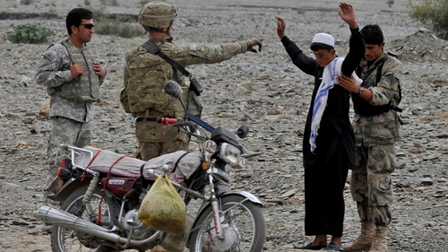 An Afghan Border Security soldier searches an Afghan man as US army soldiers look on last week