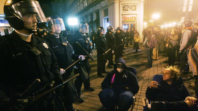 Police form a line between protesters and Frank H Ogawa Plaza during the eviction of the Occupy Oakland camp