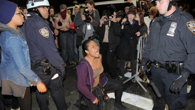 A woman yells at NYPD officers as the camp is cleared