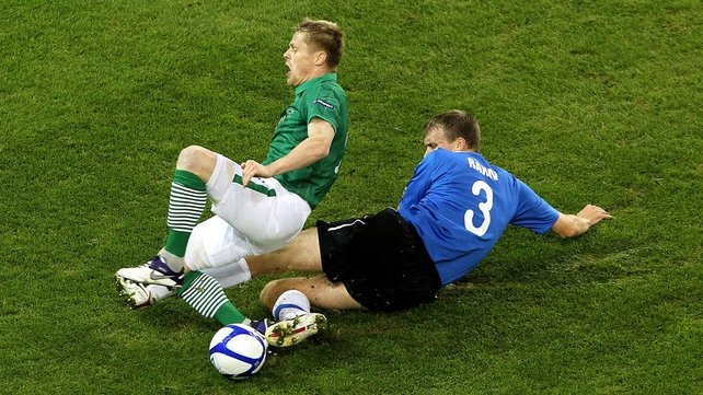 Estonia's Taavi Rahn picked up a booking for this robust challenge on the impressive Damien Duff