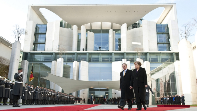 Enda Kenny and Angela Merkel review an honour guard during a welcoming ceremony at the chancellery in Berlin