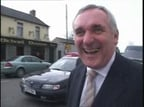 Bertie Ahern with a pub called Michael Noonan in the background.
