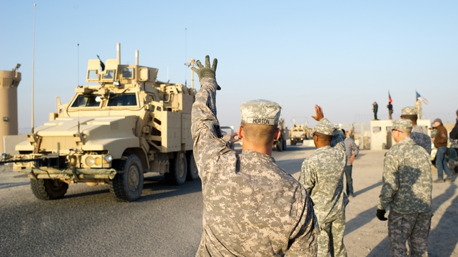 US soldiers waves at their comrades as they cross the border between Iraq and Kuwait