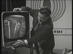 Presenter Justin Keating demonstrates how to adjust a television set on 'Telefís Feirme'.