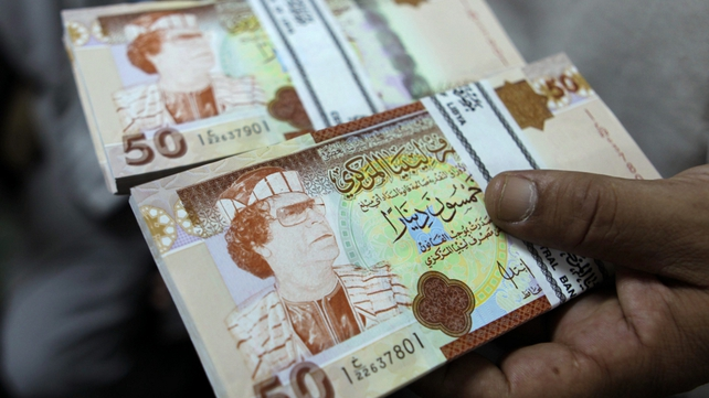 A banker shows 50 Libyan Dinar bank notes bearing the image of ousted leader Moamer Gadaffi