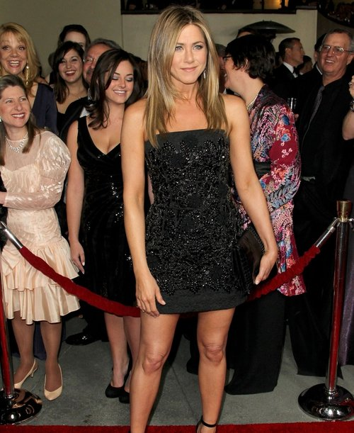 Aniston showing off her gloriously tanned skin and limber legs and arms in her black minidress