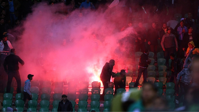 Flares are thrown in the stadium during clashes