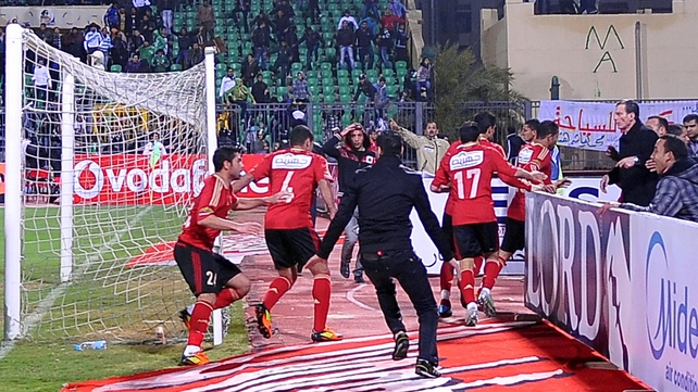 Fans of Al-Masry team chase players of the Al-Ahly team after the match