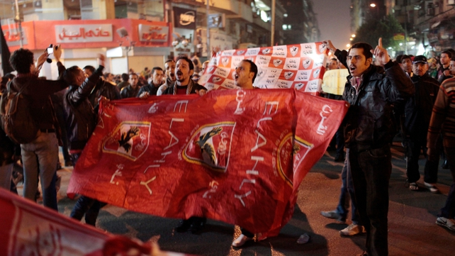Protesters hold an Al Ahly football club flag during a march to the Interior Ministry