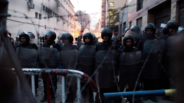 Egyptian riot police stand in formation behind barbed wire in Cairo