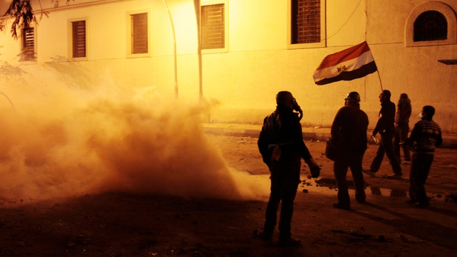 Protesters stand in clouds of tear gas fired by security forces in Cairo