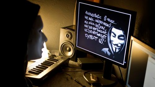 A masked hacker, part of the Anonymous group, hacks the French presidential Elysee Palace website on 20 January