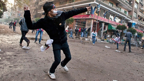 A protestor throws a rock at Egyptian security forces