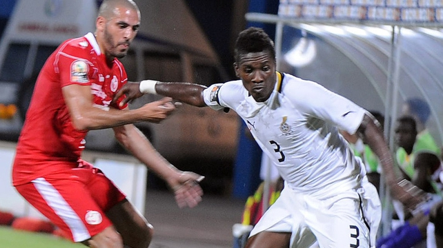 Ghana's Asamoah Gyan holds off Tunisia's Houcine Ragued in Sunday's quarter-final