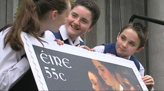 Members of RTÉ Cór na nÓg hold a large size version of the 55 cent they appear on.