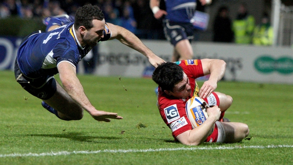 Scarlets Dan Newton touches down despite the best efforts of Leinster's David Kearney