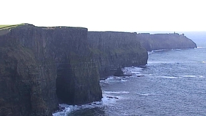 The surfer made it to shore beneath the Cliffs of Moher, which extend to 700 feet above him