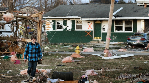 A boy searches through the rubble in Illinois
