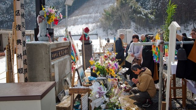 A man prays in front of a shrine for the victims from the Okawa Elementary School in Ishinomaki. Of the 108 students, 74 died and three remain missing.