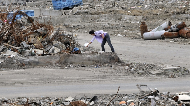 A women lays flowers for the victims in Kesennuma