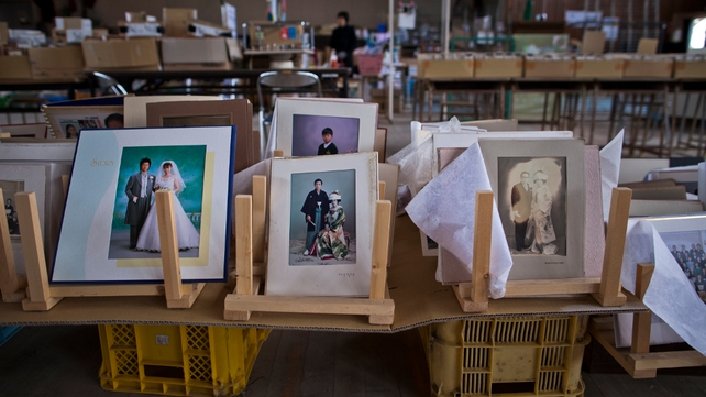 Photographs lay in a school gymnasium set up as a collection site for lost possessions in Yuriage, Natori
